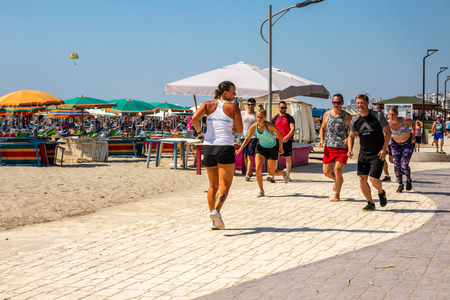 DURRES ALBANIA, AUGUST 5, 2018: Front view of a female instructor and group of people running at a beach path outdoors in Durres Albania August 5, 2018. Incidental people in the background. Editorial