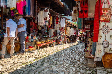 KRUJA, ALBANIA - AUGUST 10, 2018: Perspective view of people in a medina street market with souvenirs, craft items and small shops in Kruja Albania August 10, 2018. Editorial