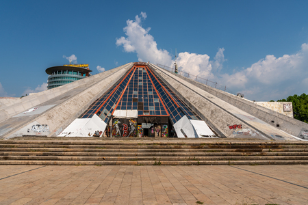 TIRANA, ALBANIA - AUGUST 10, 2018:  Exterior front view of The Pyramid of Tirana in Albania August 10, 2018. Worn, broken  and covered with graffiti. Bank sign in the background.