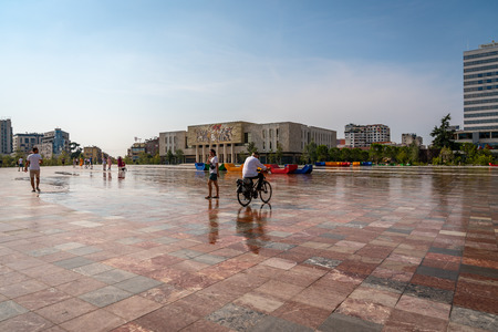 TIRANA, ALBANIA - AUGUST 10, 2018: Side view of the National Historic Museum in Tirana Albania August 10, 2018. Incidental people passing by in the foreground and a man riding a bicycle.