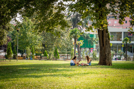 TIRANA, ALBANIA - AUGUST 10, 2018: Front view of two young woman sitting resting under a large tree in a city park in Tirana Albania August 10, 2018. Incidental people and buildings in the background. Editorial