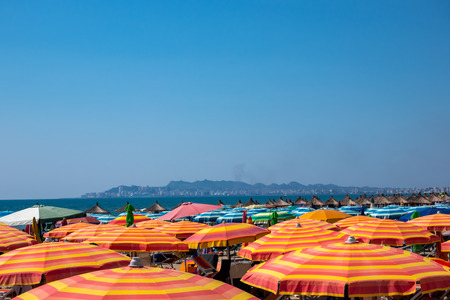 Many colorful sun umbrellas and parasols on a beach in Albania with horizon and city in the background. Stock Photo