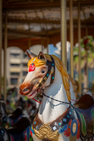 Front closeup selective focus of a merry go round horse outdoors. Stock Photo