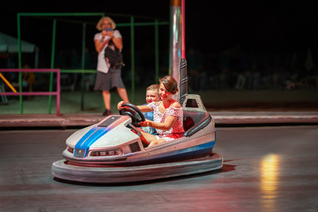 Young girl and boy driving a bumper car at a amusement park at night. Stock Photo