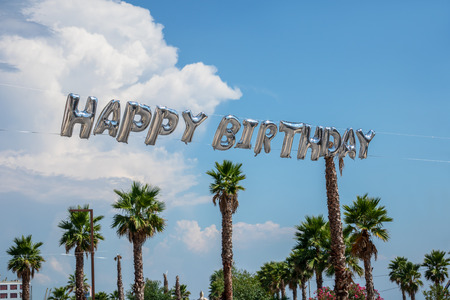 Big helium balloon letters in the air celebrating happy birthday outdoors with palms and blue sky.