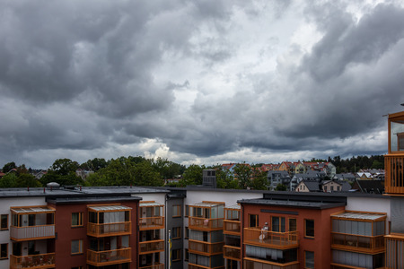 Dark summer  storm clouds over residential city buildings and rooftops. Stock Photo