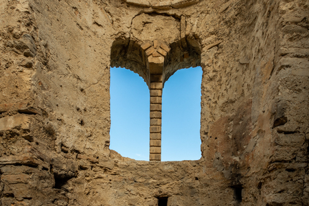 Inside of ancient stone brick ruin building with arched window and blue sky. Stock Photo