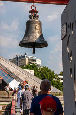 TIRANA, ALBANIA - AUGUST 10, 2018: Back view of a group of tourists walking in line under a memorial bell outdoors in a city square in Tirana Albania, August 10, 2018.