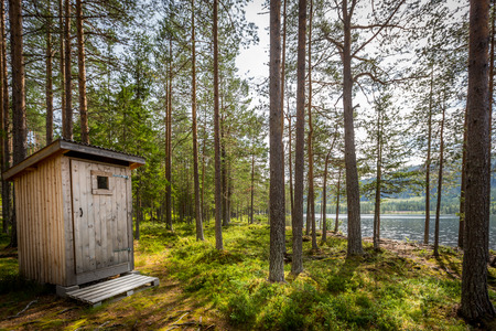 Outdoor wooden toilet in a beautiful sunny forest wilderness landscape by a lake. Stock Photo