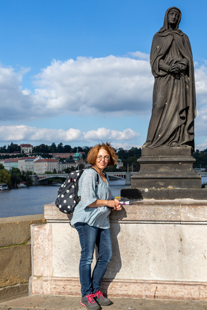 Female backpacker tourist posing next to a statue on Charles bridge i Prague Czech Republic.