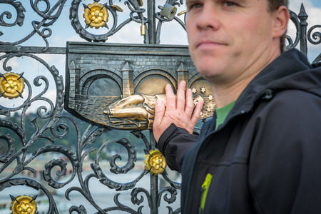 PRAGUE, CZECH REPUBLIC - SEPTEMBER 27, 2014: Closeup frontview with selective focus of a male holding his hand against a decorative bronze plaque on a fence in Prague Czech Republic September 27, 2014. Related to the legend of good luck when touching the