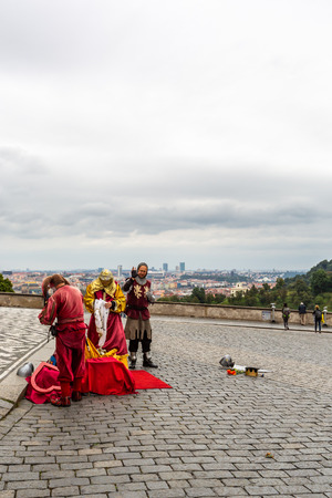 PRAGUE, CZECH REPUBLIC - SEPTEMBER 26, 2014: Three male street performers wearing traditionnal medieval clothing otdoors on a cubblestone square next to Prague castle in Prague Czech Republic September 26, 2014. Incidental people and the city in the backg