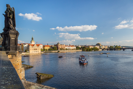PRAGUE, CZECH REPUBLIC - SEPTEMBER 27, 2014: Cityscape view of a cruise ship seen from Charles bridge with a statue in the foreground and the city in the background in Prague Czech Republic September 27, 2014. Editorial