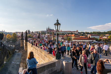 PRAGUE, CZECH REPUBLIC - SEPTEMBER 27, 2014: High angle view of a crowd of people walking on the famous Charles bridge with Prague Castle in the background.  Prague Czech Republic September 27, 2014. Editorial