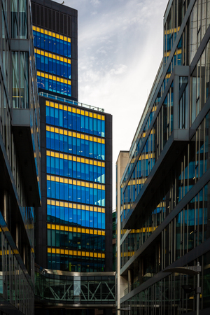 DUBLIN, IRELAND - APRIL 21, 2016: Front street view of office and business buildings with blue and yellow glass window facades in the city of Dublin Ireland April 21, 2016.