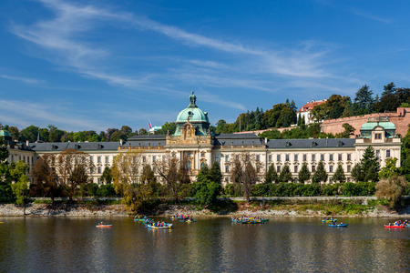 PRAGUE, CZECH REPUBLIC - SEPTEMBER 28, 2014: Front view of Straka Academy, Government of the Czech Republic. Seen from the waterside with many people canoing on the river in the foreground, Prague September 28, 2014.