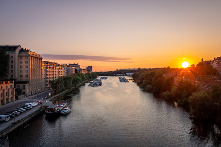 Beautiful golden summer sunset in Stockholm sweden. Perspective of water canal with boats and buildings on the side. Stock Photo