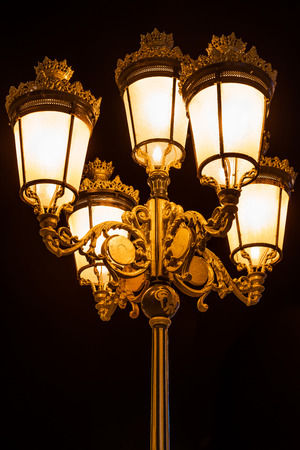 Night view of five beautiful decorative bronze street lights together on a lampost outdoors.