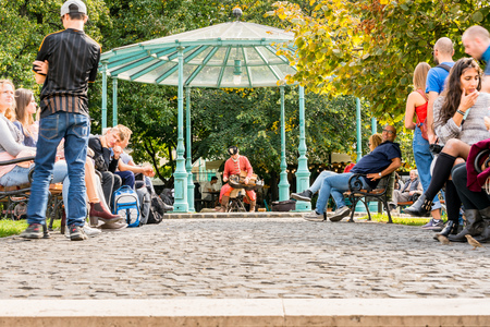 BUDAPEST, HUNGARY - SEPTEMBER 27, 2017: Low ground view of people resting in a public park. A male street performer in the middle playing an old traditional instrument in Budapest Hungary September 27, 2017.