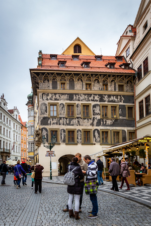 PRAGUE, CZECH REPUBLIC - SEPTEMBER 26, 2014: Outdoor front view of three people reading a map on a cobblestone square with decorative buildings in the old town of Prague Czech Republic September 26, 2014. Incidental people in the background.