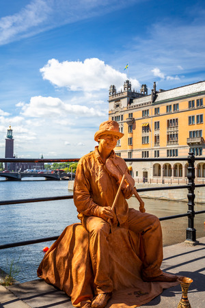STOCKHOLM, SWEDEN - JULY 11, 2014: Outdoor closeup of a male street performer on a bridge wearing makeup and gold colored clothing playing a instrument, buildings in the background Stockholm Sweden July 11, 2014.