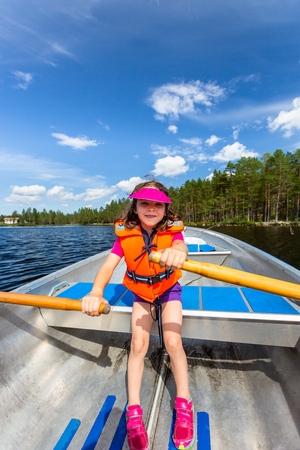 Cute young girl rowing a rowboat on a lake with blue summer sky in the background. Stock Photo