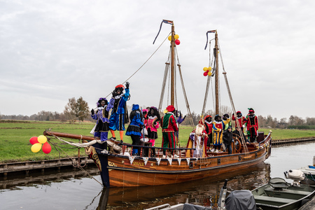 GIETHOORN, NETHERLANDS - NOVEMBER 24,  2018: Traditional festival celebration of Sinterklaas, Black Peter. People with makeup and colorful costumes on a wooden boat on a canal in Giethoorn Netherlands November 24, 2018.