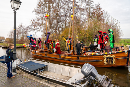 GIETHOORN, NETHERLANDS - NOVEMBER 24,  2018: Traditional festival celebration of Sinterklaas, Black Peter. People with makeup and colorful costumes on a wooden boat on a canal in Giethoorn Netherlands November 24, 2018. Incidental people in the foreground