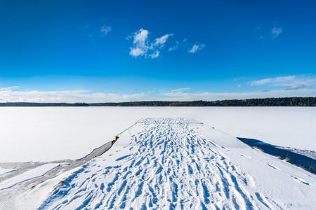 Beautiful panorama winter landscape view of blue sky and frozen snow lake and a jetty with footprints in the snow. 免版税图像
