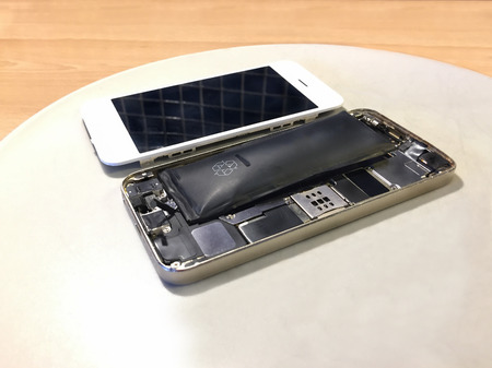 Close up inside of a damaged broken and bloated mobile phone battery with loose display beside.