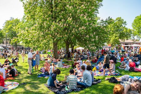 JAKOBSBERG, SWEDEN - JUNE 6, 2019: Close-up summer garden view of groups with many people and families outdoors at a green field having picnic on the Swedish national day. Diversity with mixed ages in Jakobsberg Sweden June 6, 2019.