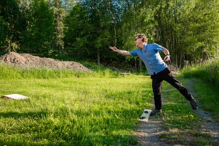 Profile view of one caucasian male in blue shirt throwing a disc on a lawn field. Traditional Swedish summer activity leisure garden game.