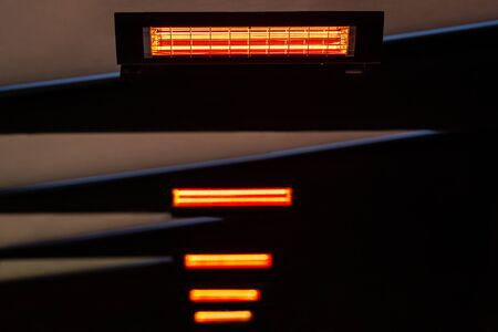 Selective focus and perspective view of many infrared heaters in the ceiling. Abstract construction with orange glow.