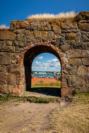 Summer view through an old medieval stone wall arched gate at Varberg Fortress in Sweden with the city and harbor in the background. 版權商用圖片