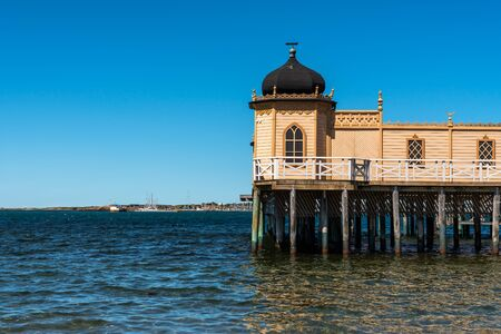 Summer seaview of the famous old historic wooden bathhouse Varbergs Kallbadhus. A cold water public bath located in the ocean with a bridge ashore in Sweden.