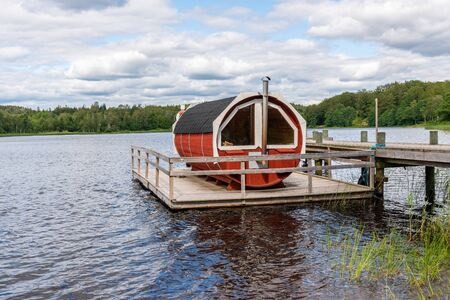 Summer lake nature landscape view of a traditional scandinavian water floating red wooden sauna spa next to a jetty.