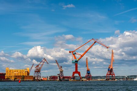 Summer seascape view of harbor cranes and dock against blue cloudy sky in Gothenburg Sweden. Stock Photo