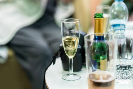 Candid snapshot of champagne glass and bottles on a small table. Traveler with camera taking a break resting with refreshments. Banque d'images - 132552198