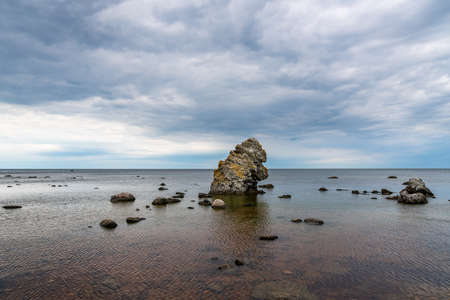 Famous rauk rock and stone formation in the shape of animal ape head with horizon of water and sky in the background at the island Gotland in Sweden. Stock Photo