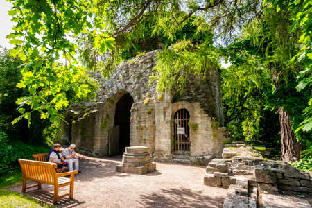 VISBY, SWEDEN - JULY 27, 2020: A senior couple sitting on a bench next to the entrance of an ancient ruin surrounded by trees in a city park in Visby Gotland Sweden July 27, 2020. Editorial