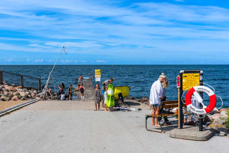 VISBY, SWEDEN - JULY 27, 2020: Front view of children and adults bathing in the Baltic Sea ocean from a concrete jetty with the horizon in the background in the city of Visby Gotland July 27, 2020.