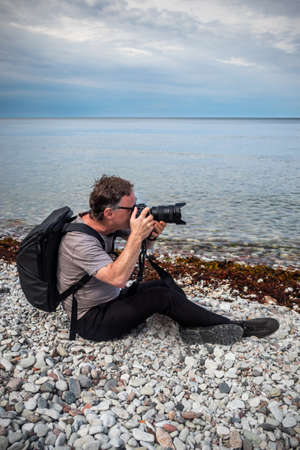 A caucasian male tourist photographer sitting on pebbles stone beach by the water with horizon in the background on the island Gotland in the Baltic Sea.