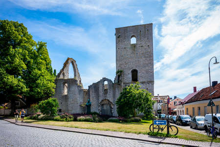 VISBY, SWEDEN - JULY 27, 2020: Beautiful summer city view of an old ancient church ruin with incidental people in the foreground in the city of Visby Gotland Sweden July 27, 2020.