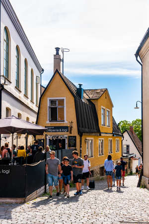 VISBY, SWEDEN - JULY 27, 2020: Summer city view of people at the famous landmark building cafe restaurant Strykjarnet in the old ancient city Visby, Gotland Sweden July 27, 2020. People passing by on cobblestone street.