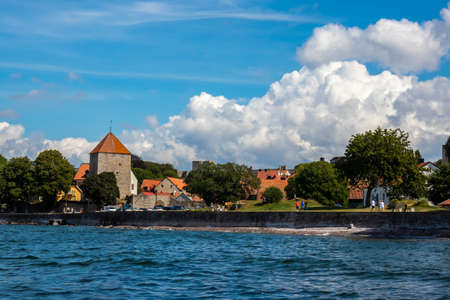 VISBY, SWEDEN - JULY 27, 2020: Beautiful summer seaside view of the old ancient city Visby. Recreation park area with people walking next to the sea in Visby Gotland July 27, 2020.