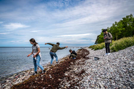 A family playing and throwing stones at a pebble stone beach at Gotland with water horizon and sky in the background.