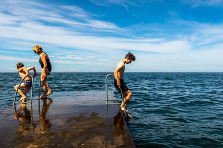 Summer view of a family on a stone jetty about to  swim in the ocean of the Baltic Sea with blue sky and horizon in the background.