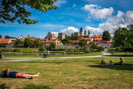 VISBY, SWEDEN - JULY 27, 2020: Beautiful summer landscape view of Almedalen garden and recreation park area. People sitting and lying in the grass in Visby Gotland July 27, 2020.