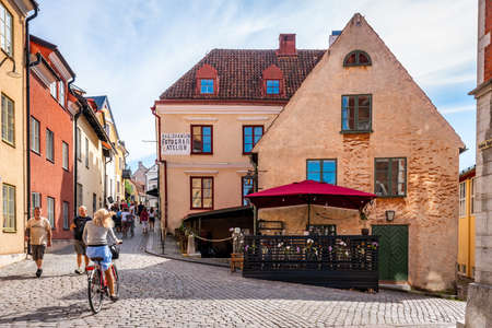 VISBY, SWEDEN - JULY 27, 2020: City view of a cafe restaurant on cobblestone street with old ancient buildings in the city of Visby Gotland July 27, 2020. People and a female cyclist next to the cafe.