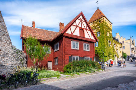 VISBY, SWEDEN - JULY 27, 2020: Summer city view of an old red wooden gothic alp building in the historical city Visby, Gotland Sweden July 27, 2020. Incidental people walking by on cobblestone street. Editorial